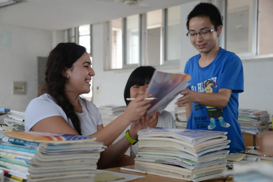 Engineering student Lola Buonomo writes some English in a Chinese student's notebook during the Penn State class's visit to a secondary school in Huangshan. (Photo credit: Curtis Chan)