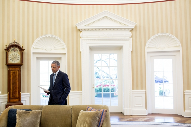 President Barack Obama looks over paperwork between meetings in the Oval Office. (Photo credit/Pete Souza, Official White House photo)