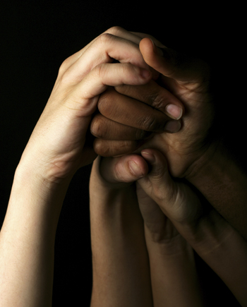 four hands clasped together and raised up on a black background