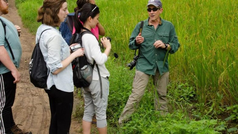 Man in field speaking to four students