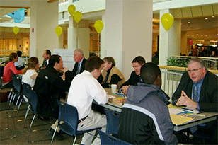 Students talking to alumni and professionals at table