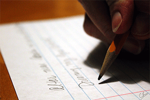 person writing on a sheet of paper