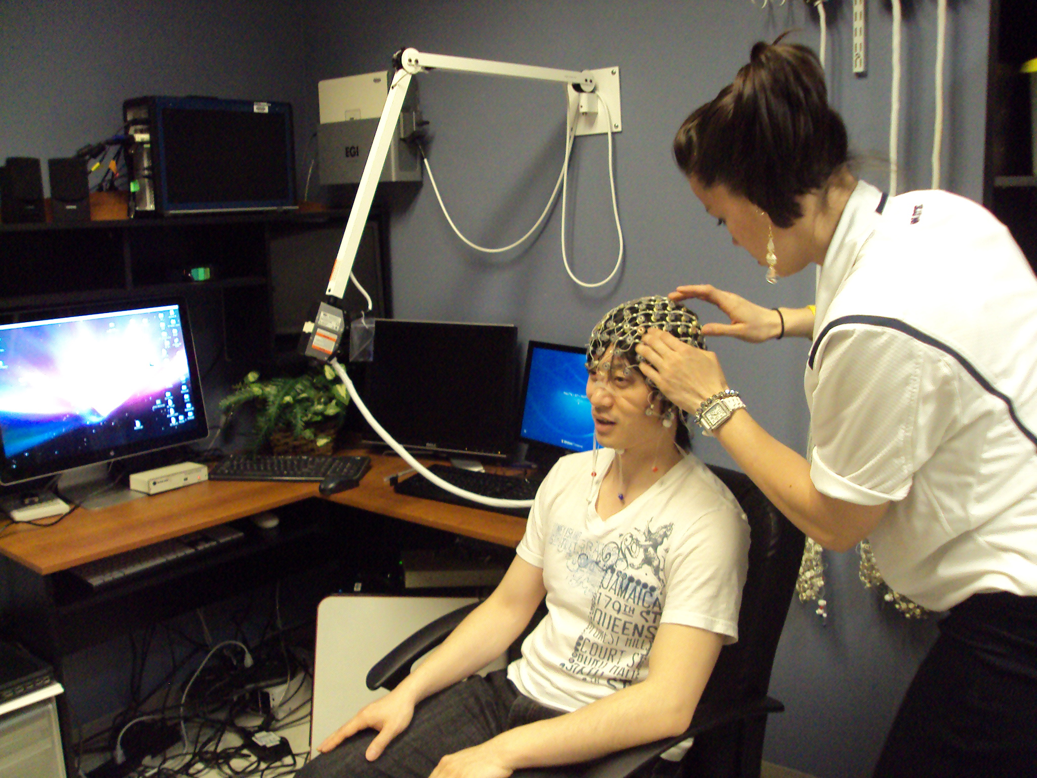 woman fitting EEG cap on volunteer
