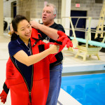 Buzz Scott, Founder and Executive Director of OceansWide, helps Penn State Science Education Program Associate Jessica Kim-Schmid into an immersion suit during an aquatic Polar Day demonstration at Penn State's Natatorium. Photo by Michelle Bixby.