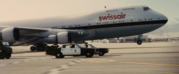 Iranian police cars match speed with a 747 at takeoff.
