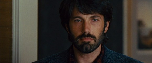 As CIA agent Tony Mendez, Ben Affleck gazes meaningfully back at the six diplomats he is trying to rescue.  Still from DVD of Argo, directed by Ben Affleck, produced by Warner Brothers.