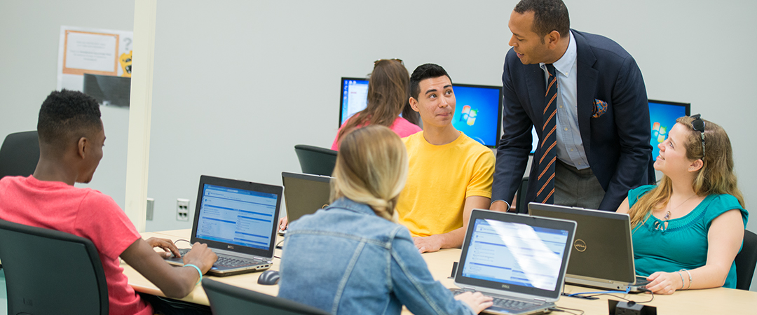 A professor talks to a group of students using laptops at Penn State Brandywine.