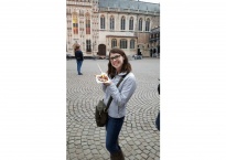 Rachel holding a waffle in front of a building in Bruges