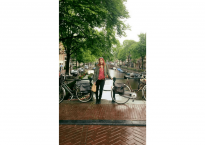 Jamie with a bike in front of a canal in Amsterdam