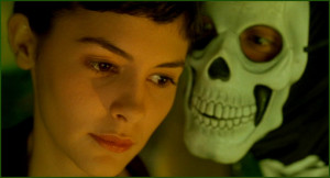 Amélie is on a haunted amusement park ride in this picture where a man in a skeleton mask is face to face trying to terrify her, but she remains unfazed