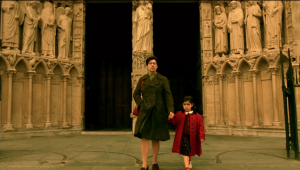 Six-year-old Amelie holding her mother's hand as they leave Notre Dame. The doors are visible in the background.