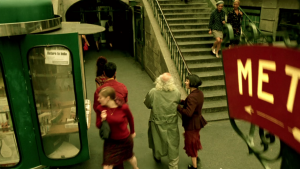 Amelie leading a blind man down a street.