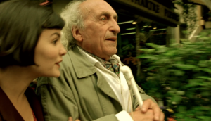 A blind man is being led by the arm by Amelie. The background is blurred to show that she is rushing him down the street.