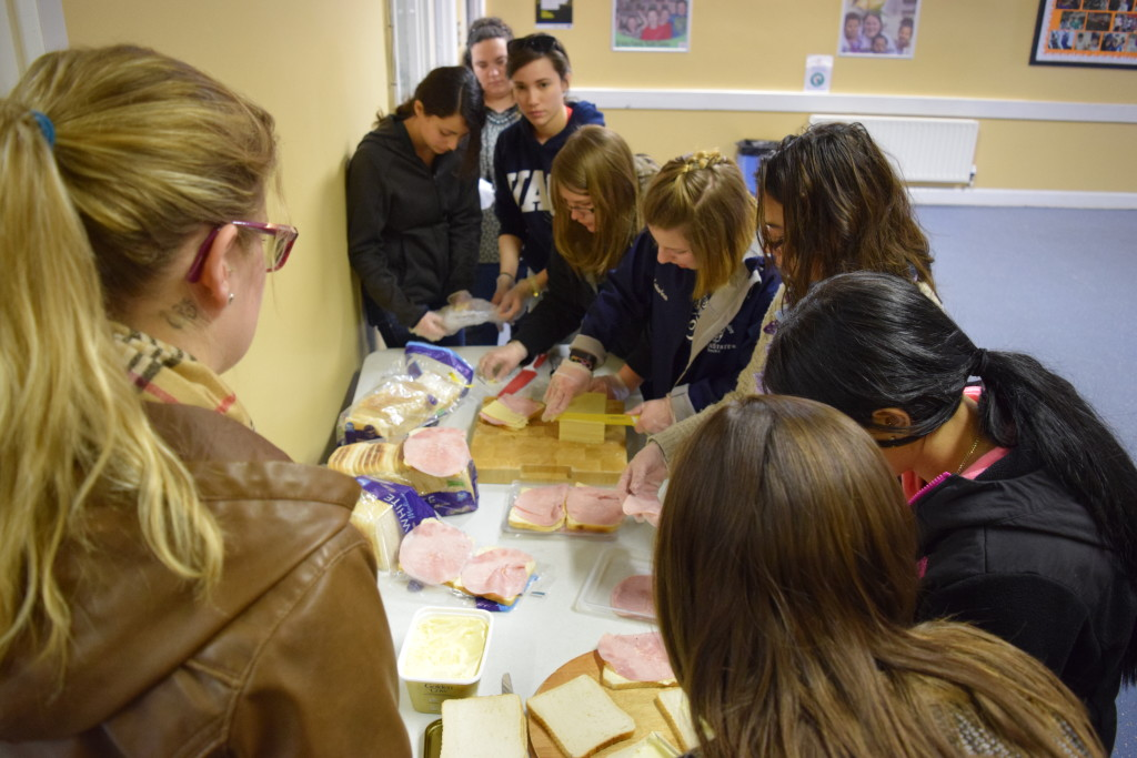Students work at Holy Family Youth Center to pack lunches for the homeless community in Belfast, Ireland.