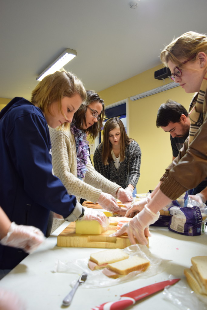 Students cheerfully crowd around a table to make sandwiches for the homeless.