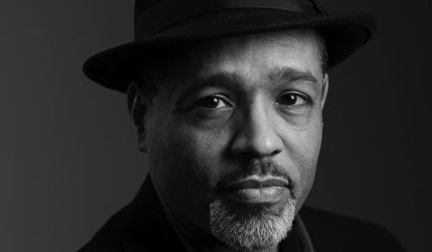 A black and white photograph of Steve wearing a fedora and looking directly at the viewer.