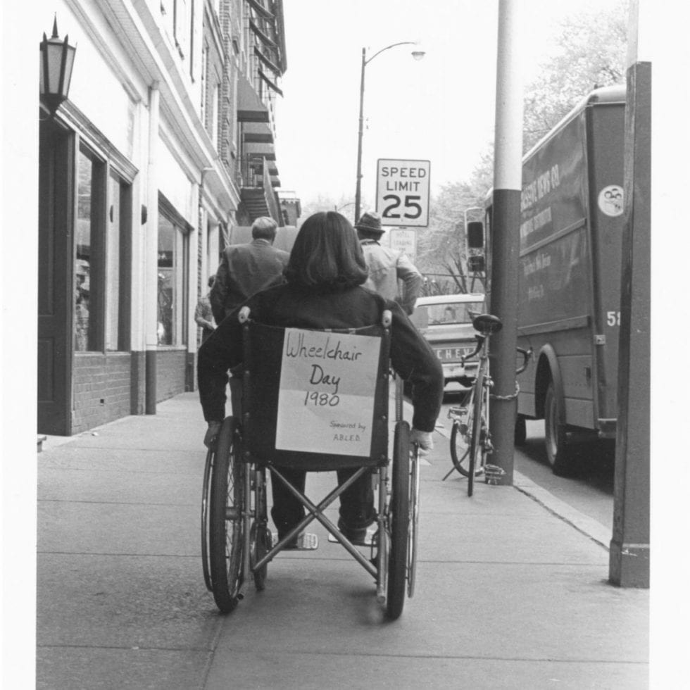 Black and white photograph of wheelchair from behind