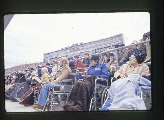 Color photograph of people in wheelchairs watching event at Beaver Stadium