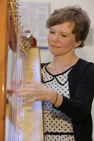 Mary-Kate Spring of the Celtic folk band Seasons plucks the strings of her floor standing wooden harp in the Penn State Cancer Institute lobby.