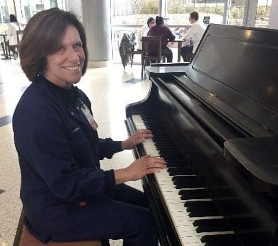 Employee, Cheryl Foelker, RN, BSN plays the piano in the main entrance lobby