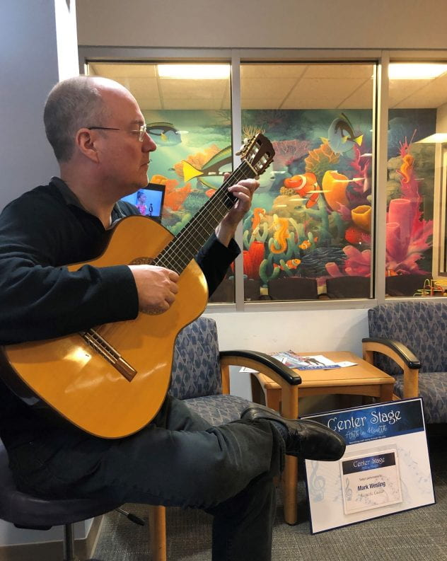 Mark wesling plays guitar in the lobby of the UPC