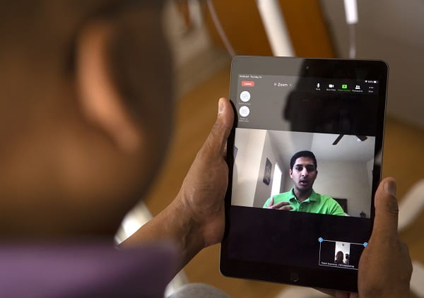 Maurice Brown, of Harrisburg, chats with Rahul Gupta, a fourth-year medical student at the College of Medicine, via an iPad from his room in Penn State Cancer Institute.