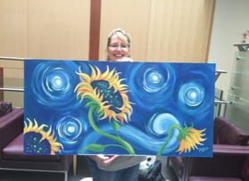 Mary Fusco proudly dispalys her recent painting