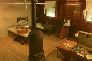 1942: Luggage From Home To Camp, 2003, 20' x 20', mixed media: barrack, suitcases, windows, potbelly stove