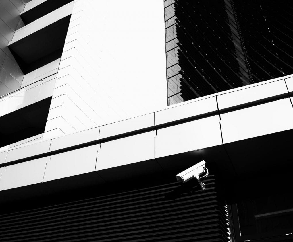 black and white photo of surveillance camera mounted on a building