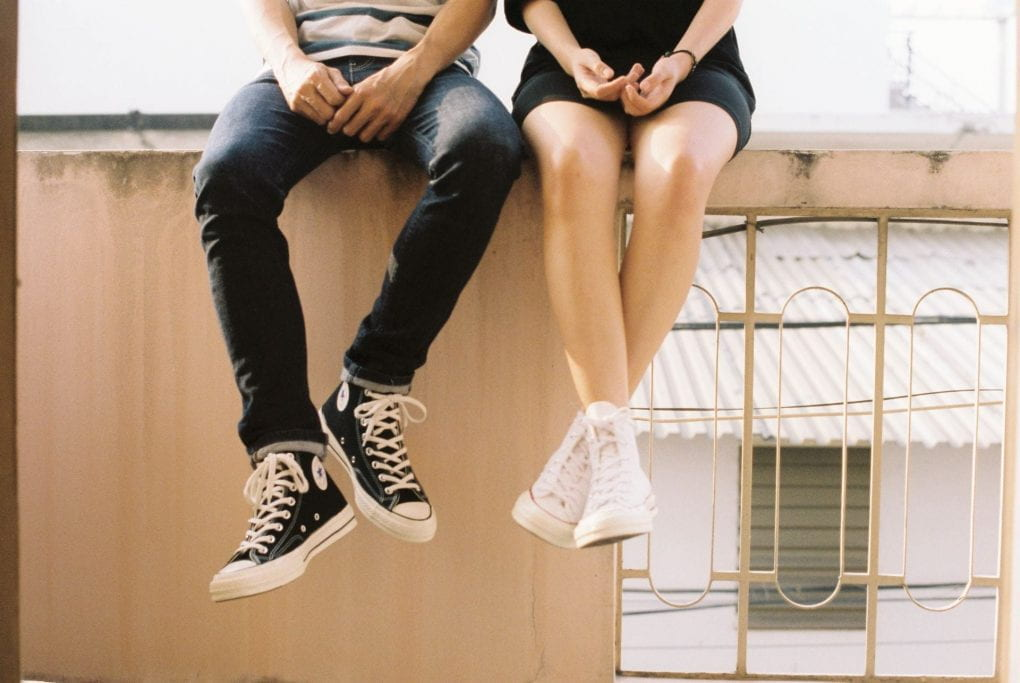 Two people sitting on ledge with legs hanging over the edge with only lower bodies visible