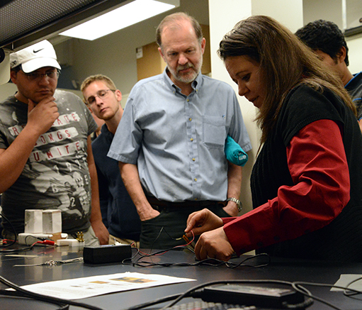 Zoubeida Ounaies, the Dorothy Quiggle Professor of Mechanical Engineering, right, demonstrates a how a piece of piezoelectric material can be turned into a music speaker to origami expert Robert Lang, center. (Photo credit: Curtis Chan)
