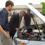 Penn State President Eric Barron gets an update on Penn State's EcoCAR competition vehicle from Advanced Vehicle Team members  Ben Sattler and Chris Monaco.