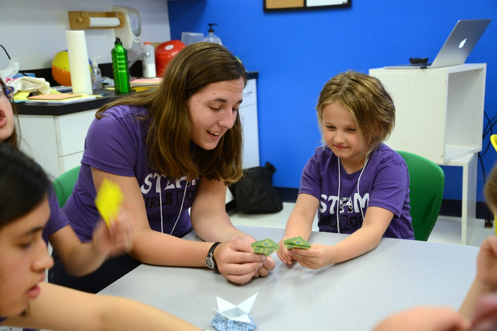 A girl gets some hands-on experience in the art of origami during the Discovery Space's day camp focused on science, technology, engineering and mathematics for girls. (Photo credit: Curtis Chan)