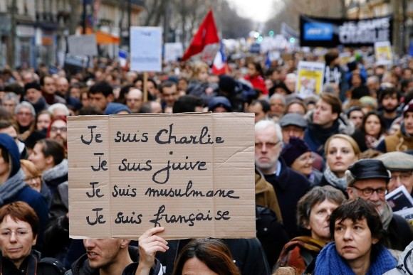 A woman holds up a sign that says, 'I am Charlie, I am Jewish, I am a Muslim, I am French' during a rally in Paris on Jan. 11. PHOTO: AGENCE FRANCE-PRESSE/GETTY IMAGES