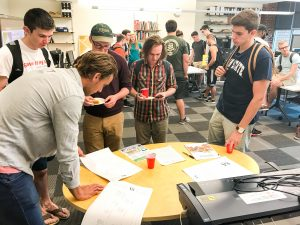 Students gather around a table and look at past competition documents.