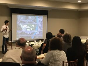 Penn State architecture student presents design work on screen in front of 35 community members in a conference room in Pottstown, PA.