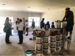 Students and professionals discussing the project inside a home under construction with paint cans around.