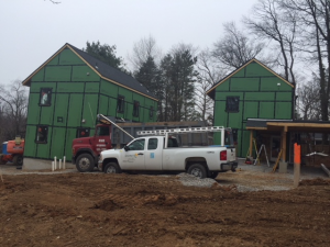 New construction of two homes with work trucks