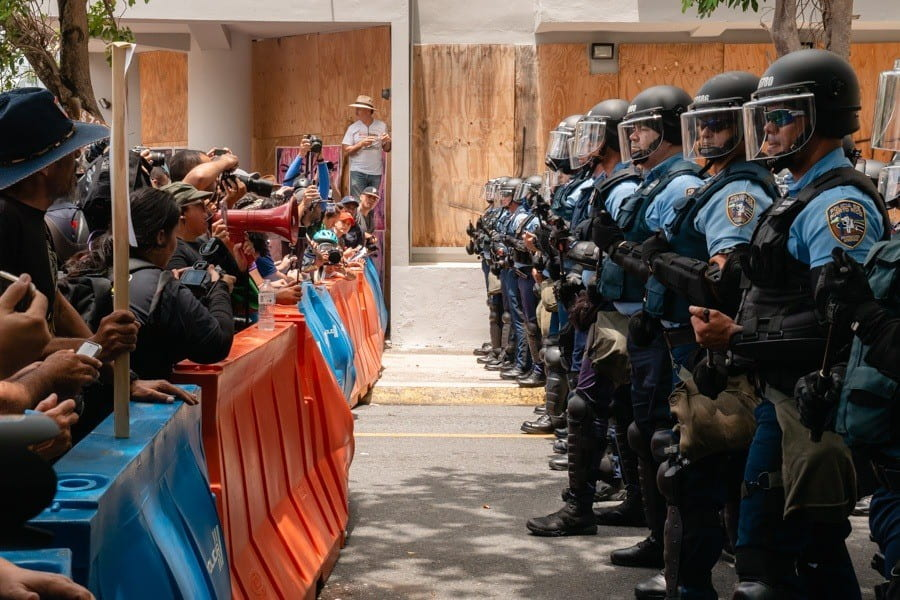 "An image from the film ""DisemPOWERed: Puerto Rico's Perfect Storm"" shows protesters stand facing police officers in Puerto Rico. IMAGE: ROQUE NONINI"