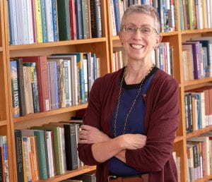 Portrait of Bernice Hausman in front of bookshelves 2019