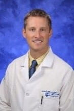 Christopher Riney head and shoulders white coat portrait