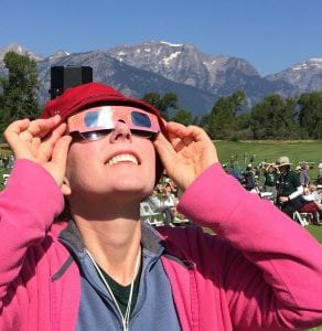 woman gazing skyward, holding eclipse glasses on top of sunglasses