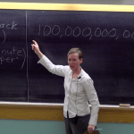 teacher at front of lecture hall, pointing to numbers written on chalkboard