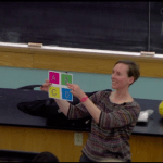 teacher smiling and holding up a brightly colored piece of paper with the letters A, B, C, and D in large font