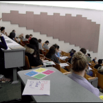 view of a large lecture hall from the back, showing rows of seated students looking forward