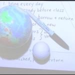 projector screen at front of lecture hall showing a closeup view of a small model Earth ball, golf ball, and a marker for size reference