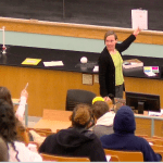 teacher piece of paper up high, looking over her shoulder at students, and one student is pointing at the paper