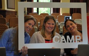 Three attendees of a past camp peering through a picture frame that says camp.