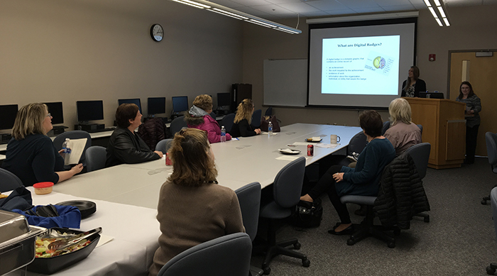 faculty and staff members sitting around a conference table watching a presentation