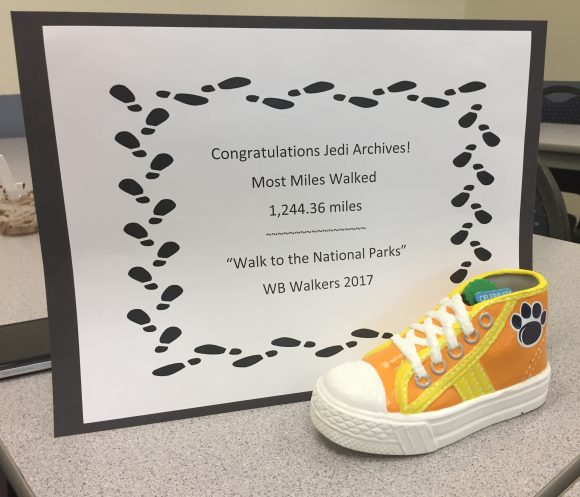 image of small yellow high-top sneaker in front of award certificate for Most Miles Walked competition